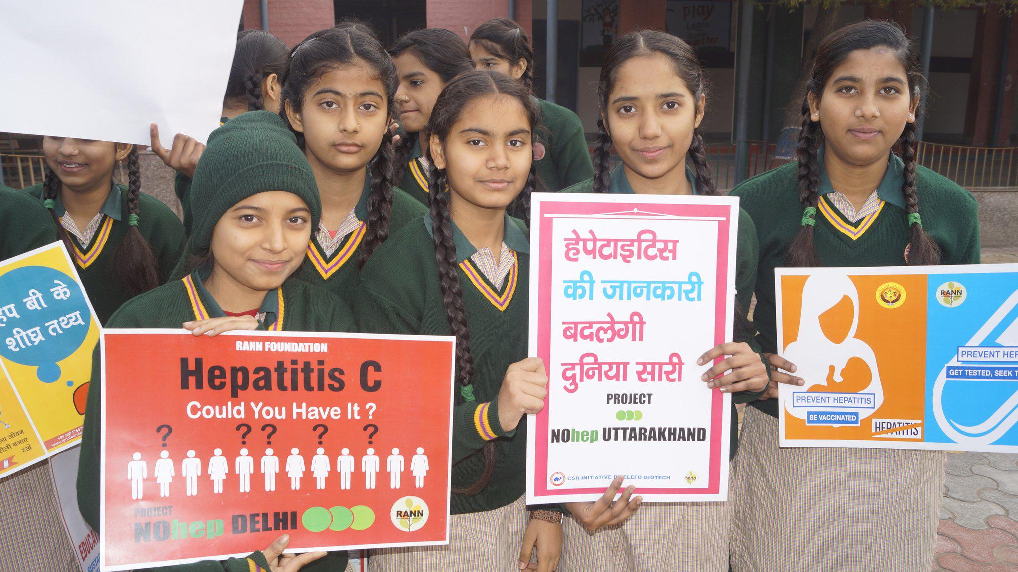 Schoolchildren holding up information about viral hepatitis